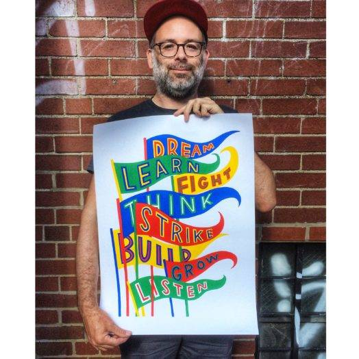 Artist and designer Josh MacPhee holding a poster depicting pennants that list the words dream, learn, fight, think, strike, build, grow, listen